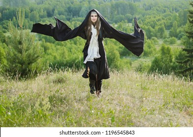young witch in black robes waving his arms and casts a spell while standing on a hill