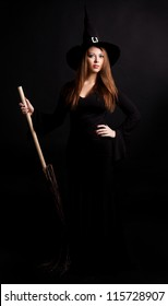 young  witch with  a broom, against dark studio background