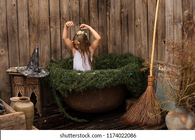 Young witch flew on broom in secluded place to plunge into cauldron with decoction of rejuvenating herbs on eve of Halloween. Concept of Witchcraft, magic, amulet, medicinal herbs, happy Halloween