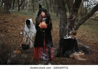 Young witch in peaked hat with a pumpkin in her hands, Halloween, Samhain