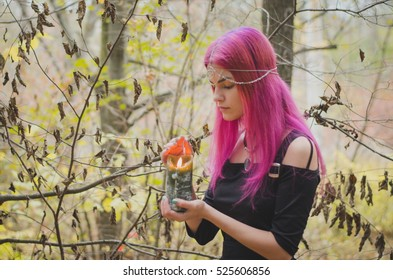Young witch with pink hair performing a magical ritual with a large green candle, faded colors, selective focus and faded colors