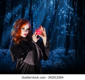 Young witch with potion at night forest