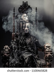 Young   witch sits on a chair. Bright make up, skull, smoke-  halloween theme.