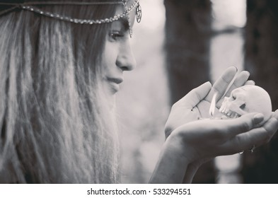 Young witch with a skull candle in her hands, black and white photo, soft focus, faded colors