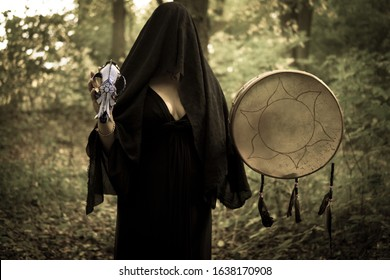 Young witch in twilight forest holding shamanic drum and wolf skull. A mysterious pagan priestess with covered face. Mystic Halloween witchy atmosphere. Occulture, magic, spiritual, witchcraft.