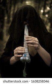 Young witch in twilight forest playing on Tibetan Kangling bone flute. A near death vision. Mysterious pagan priestess with covered face. Mystic Halloween witchy atmosphere Occulture, magic, spiritual