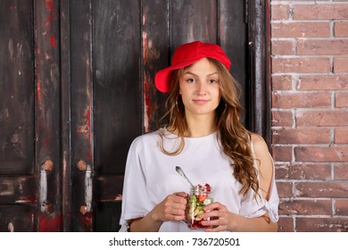 Young womam healthy lifestyle holding cup glass cut fruits, red cap, indoor loft style