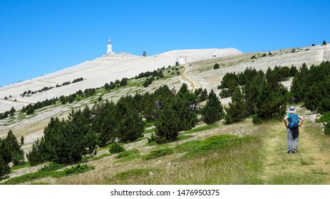 young woman (30s) with backpack is climbing Mont Ventoux, the highest peak in Provence, southern France, Europe, view during hot summer day in July, outdoor adventure in dry mountain landscape