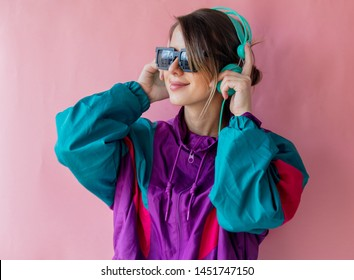 Young woman in 90s style clothes with headphones on pink background