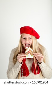 A young woman about to enthusiastically devour a gingerbread cookie