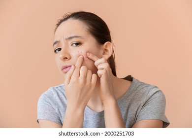 Young woman with acne problem squishing pimples on color background
