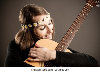 Young woman with acoustic guitar and flower hairband