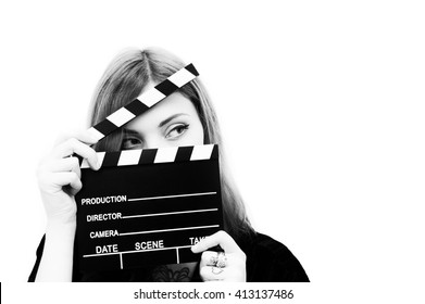 Young woman actress with movie clapper posing isolated in black and white
