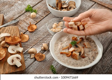 Young woman adding croutons to delicious mushroom soup at wooden table