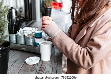 Young woman are adding sugar stick in fresh hot coffee outdoor cafe takeout