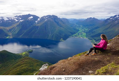Young woman admires the amazing fjord landscape from Saksa mountain (Sunnmørsalpene) in Romsdal, Norway, on a cloudy day of summer