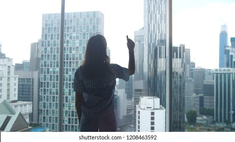 Young woman admires panoramic window looking out apartment on the city buildings