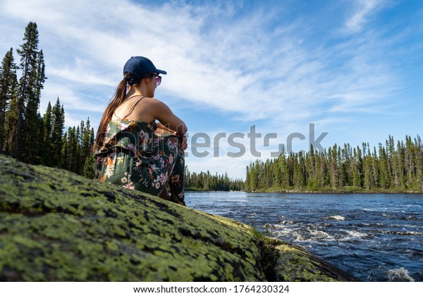 Young woman admiring a canadian river in Charlevoix