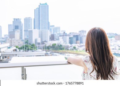 Young woman admiring the city scenery on the balcony
