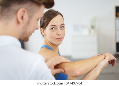 Young Woman Admiring her Male Physical Therapist While Working on her Injured Arm.