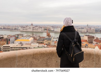 Young woman is admiring Hungarian Parliament Building from Fisherman's Bastion in Budapest, Hungary