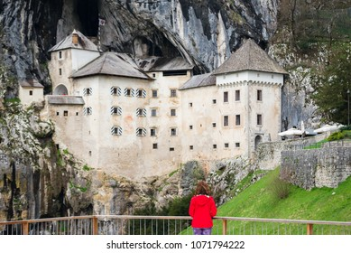 Young woman is admiring the magnificent Predjama Castle which is one of the most famous landmarks in Slovenia, attracting  thousands of tourists each year.