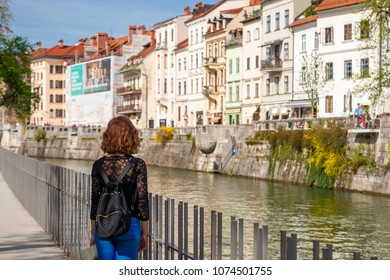 Young woman is admiring old buildings and apartments in old part of Ljubljana, Slovenia
