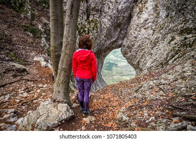 Young woman is admiring The Otlica Natural Window above Vipava valley in Slovenia