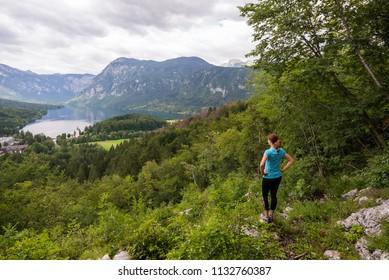 Young woman is admiring panoramic view of lake Bohinj in Bohinj, Slovenia