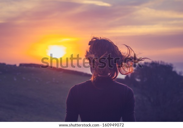 Young woman admiring the sunset over fields