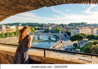 Young woman admiring the view of Rome from Castel Sant`Angelo, Italy, Europe. Beautiful panorama of Roma city in summer. Girl tourist looks at Rome from above. Concept of travel and vacation in Rome.
