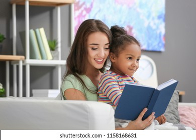 Young woman with adopted African American girl on sofa at home