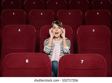 Young woman afraid of the movie at the cinema