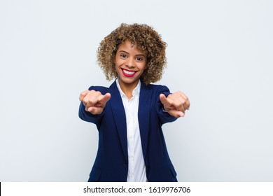 young woman african american feeling happy and confident, pointing to camera with both hands and laughing, choosing you against flat wall