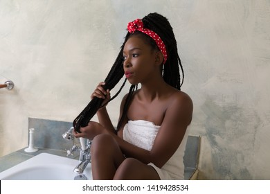 Young woman with afro hairstyle preparing to take a bath in a vintage white bathroom
