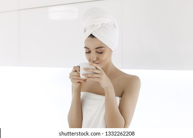Young woman after bath or shower enjoying coffee indoors at home. Young Mixed race Caucasian Asian woman with perfect makeup in white towel with cup of coffe or tea on modern light kitchen.