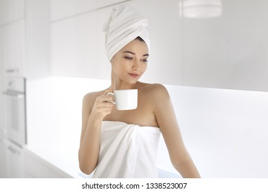 Young woman after bath or shower enjoying coffee indoors at home. Morning coffee is my daily routine. Tender photo of fresh young Mixed race Caucasian Asian woman with perfect makeup in white towel