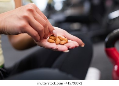 Young woman after exercising eating almonds