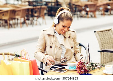 Young woman after shopping reading magazine in a cafe and listen music via headphones