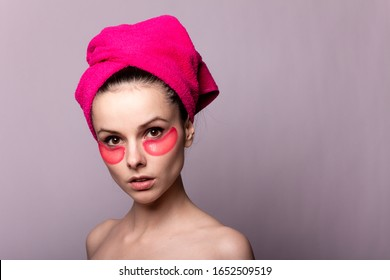 young woman after a shower in a pink towel and patches