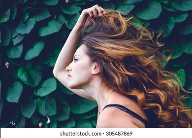 young woman against background of summer green park, green leaves.  girl with beautiful curly hair