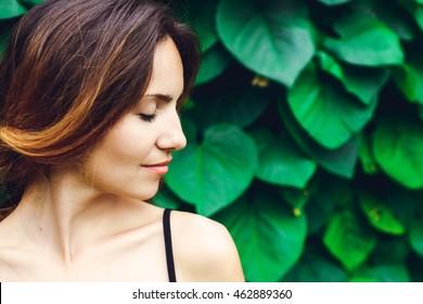 Jovem mulher, no fundo do parque verde de verão, folhas verdes. Jovem de olhos fechados.
