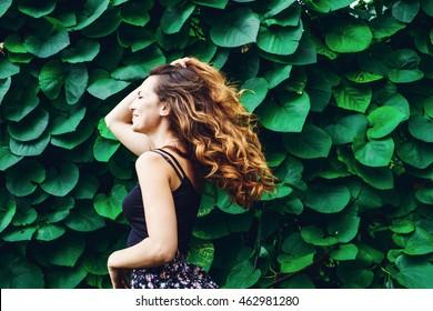 mulher jovem, contra o fundo do parque verde verão, folhas verdes. Running menina com cabelo encaracolado bonito. Mulher carinhosa.