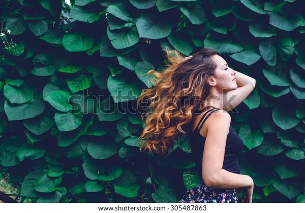 夏の緑の公園の背景に若い女性、緑の葉。美しい巻き毛の走る女の子