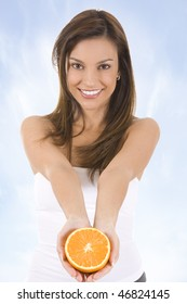 Young woman against blue sky with an orange.