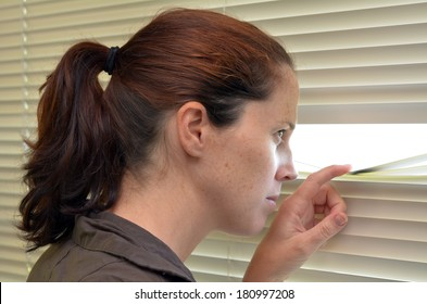 Young woman (age 25-30 ) looks out through Venetian blinds. Concept photo of curious, spy, nosy woman.