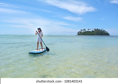 Young woman (age 30) on a Stand Up Paddle Board paddle boarding in Muri lagoon in Rarotonga, Cook Islands. Real people. Copy space