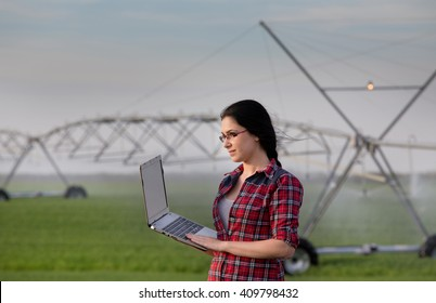 Young woman agronomist standing on field with laptop. Water irrigation system in background
