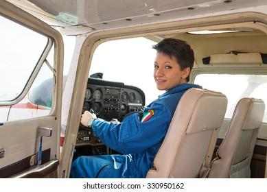 Young woman airplane pilot portrait inside cockpit.