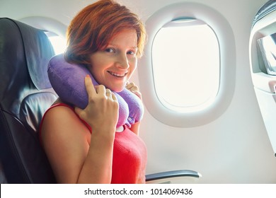 young woman in an airplane seat. traveler in an plane with pillow for neck